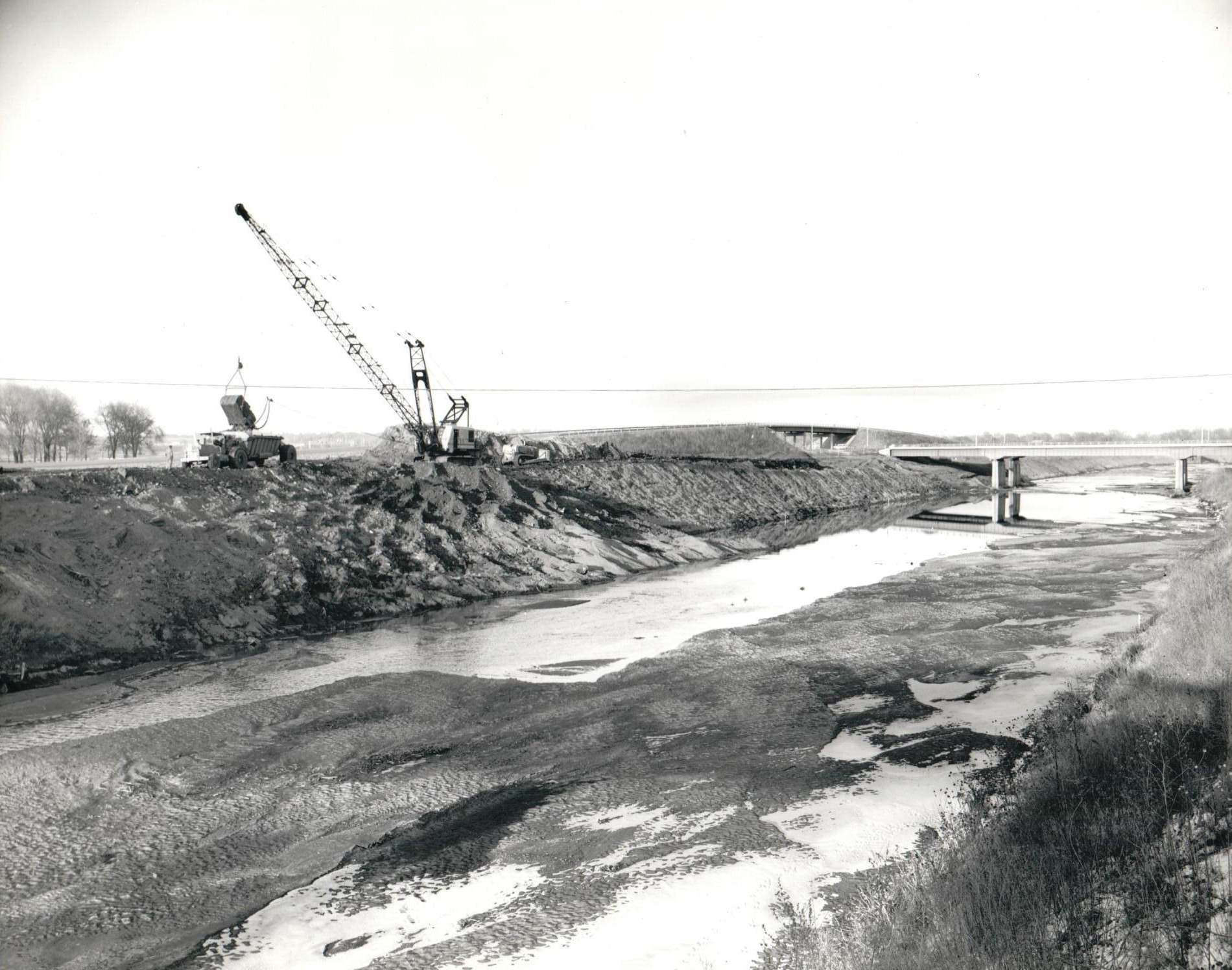 Salt Creek Levee construction in December 1964, along SYA highway (now called Sun Valley Boulevard), near Oak Lake. The Interstate 180 bridge is at right.